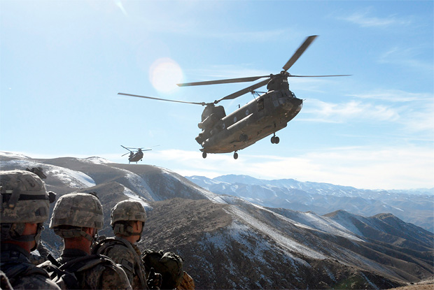 Standing by on a hilltop, soldiers with the 101st Division Special Troops Battalion, 101st Airborne Division watch as two Chinook helicopters fly in to take them back to Bagram Airfield, Afghanistan