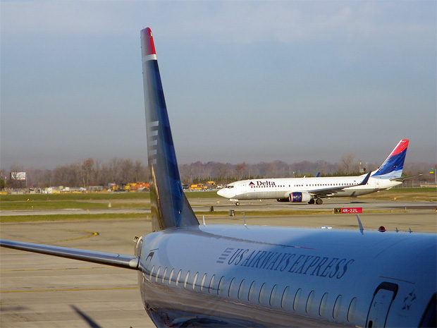 A Delta 737 taxis past a US Airways Express Embraer E-jet in Detroit
