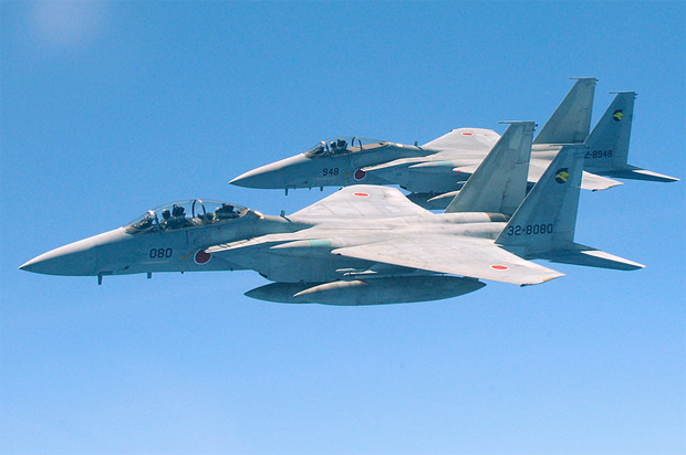 Two Japan Air Self Defense Force F-15's fly alongside a U.S. Air Force KC-135 from the 909th Air Refueling Squadron, Kadena Air Base, during air refueling training July 30