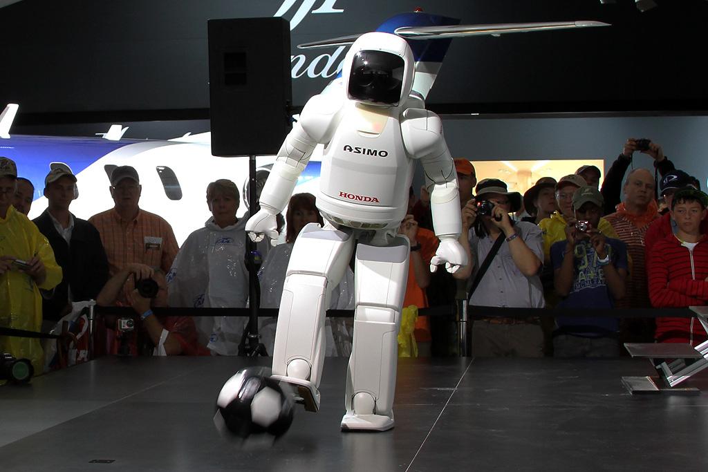 Asimo robot kicks a soccer ball