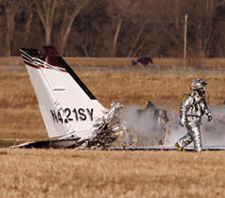 A firefighter walks passed the smoldering wreckage of the Cessna 421 (N421SY