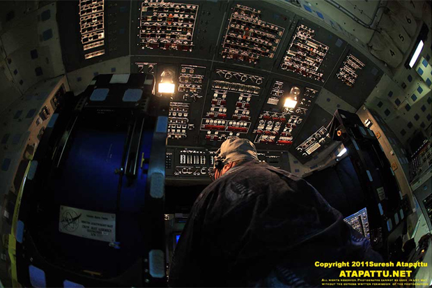 A shuttle engineer works on powering up the avionics on the flight deck of Atlantis. He is sitting between the two seats for the commander and pilot. This space would be occupied by two jump seats for two more astronauts for ascent and landing