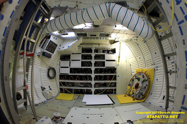 The middeck of the space shuttle Atlantis looking towards the nose of the orbiter. The two ladders on the left and right leads to the flight deck. The white duct is bring in cold air to the flight deck. The hatch cover has been removed and placed on the right side. The bays in front hold racks of storage for equipment and experiments in flight